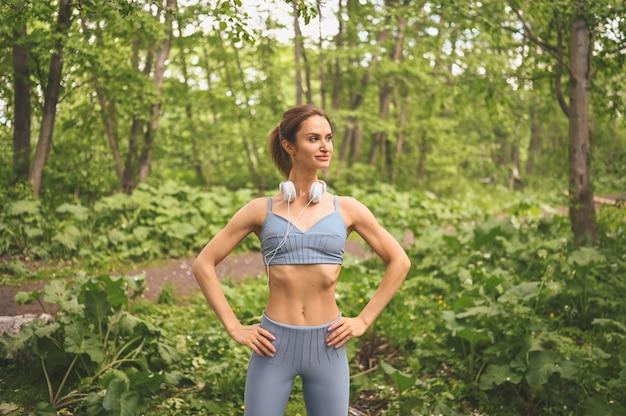Jonge mooie slim fit meisje in blauwe sportkleding met grote witte koptelefoon sport en fitness in de zomer park buiten