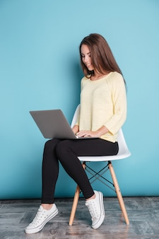 Jonge mooie slimme meid met behulp van laptop pc-computer voor studie geïsoleerd op de blauwe achtergrond