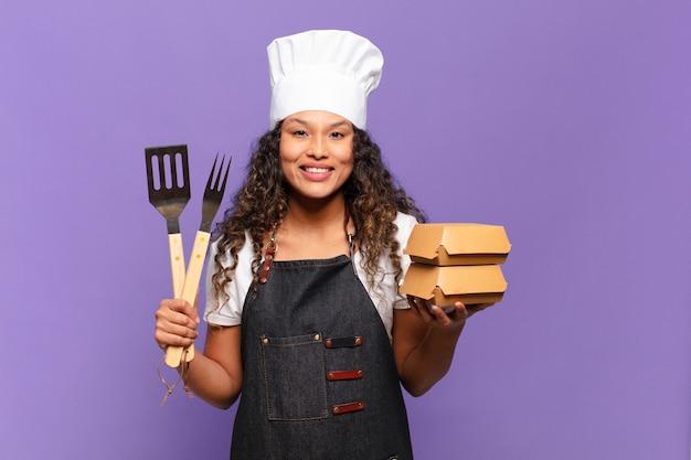 Jonge mooie spaanse vrouw blij en verrast uitdrukking barbecue chef-kok concept