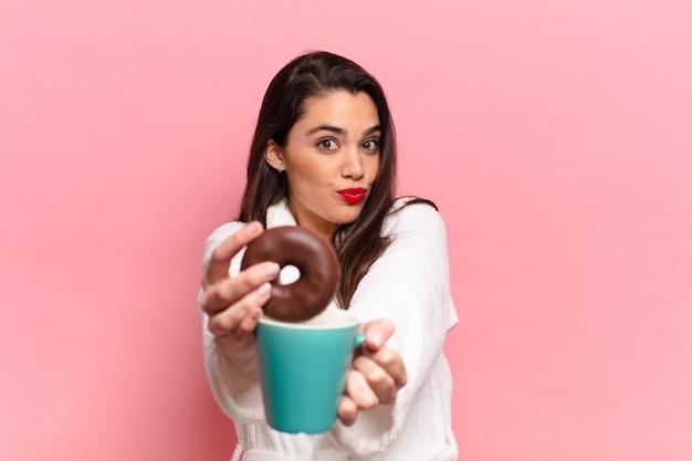 Jonge mooie spaanse vrouw blij en verrast uitdrukking met chocolade donut
