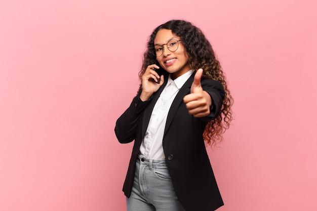 Jonge mooie spaanse vrouw. blij en verrast uitdrukkingsbedrijf en smartphoneconcept