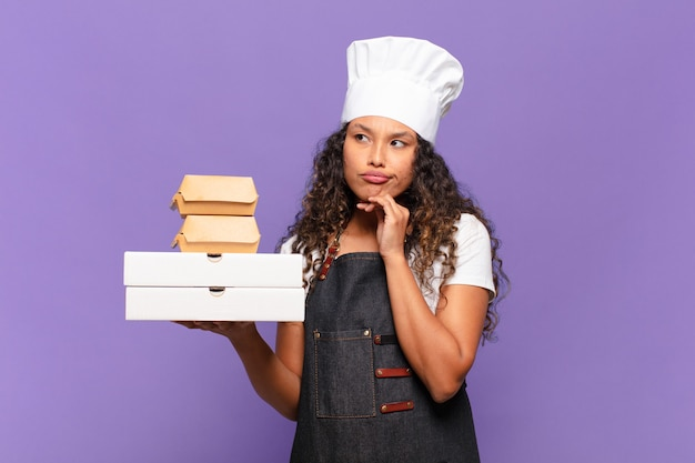 Jonge mooie spaanse vrouw. denken of twijfelen expressie barbecue chef concept