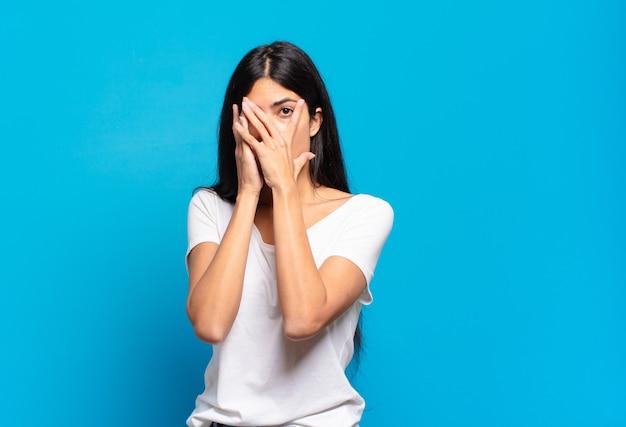 Jonge mooie spaanse vrouw die bang of beschaamd voelt, gluurt of spioneert met de ogen half bedekt met handen