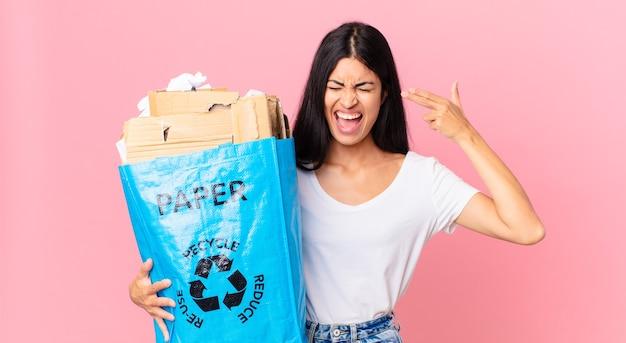 Jonge mooie spaanse vrouw die er ongelukkig en gestrest uitziet, zelfmoordgebaar maakt een pistoolteken en houdt een papieren zak vast om te recyclen