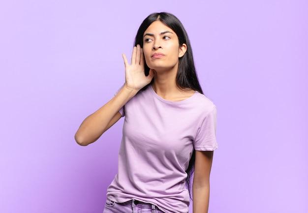 Jonge mooie spaanse vrouw die er serieus en nieuwsgierig uitziet, luistert, probeert een geheim gesprek of roddel te horen, afluisteren