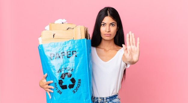 Jonge, mooie spaanse vrouw die er serieus uitziet met een open palm die een stopgebaar maakt en een papieren zak vasthoudt om te recyclen