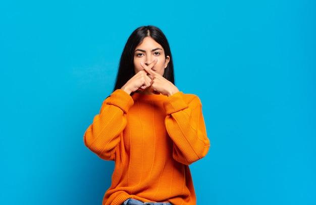Jonge, mooie spaanse vrouw die ernstig en ontevreden kijkt met beide vingers over elkaar gekruist in afwijzing, vragend om stilte