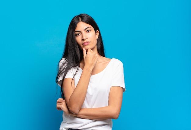 Jonge mooie spaanse vrouw die ernstig, verward, onzeker en attent kijkt, twijfelt tussen opties of keuzen