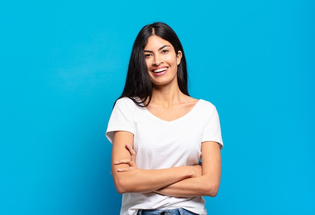 Jonge mooie spaanse vrouw die eruit ziet als een gelukkige, trotse en tevreden uitvoerder die met gekruiste wapens glimlacht
