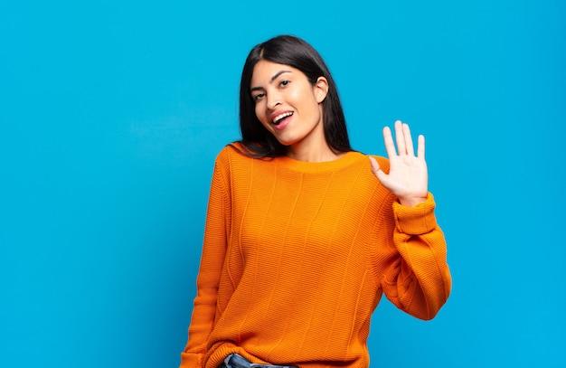 Jonge mooie spaanse vrouw die gelukkig en opgewekt lacht, met de hand zwaait en je groet, of afscheid neemt
