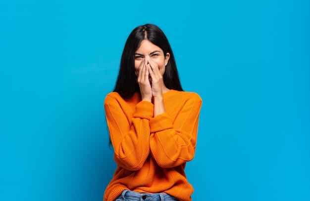 Jonge mooie spaanse vrouw die gelukkig, vrolijk, gelukkig en verrast kijkt en de mond bedekt met beide handen