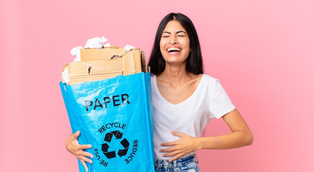 Jonge mooie spaanse vrouw die hardop lacht om een hilarische grap en een papieren zak vasthoudt om te recyclen
