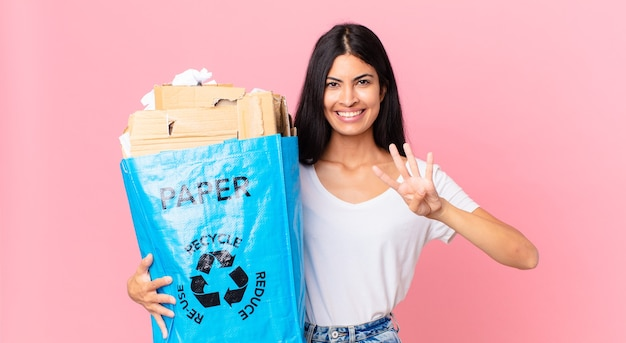 Jonge mooie spaanse vrouw die lacht en er vriendelijk uitziet, nummer vier toont en een papieren zak vasthoudt om te recyclen