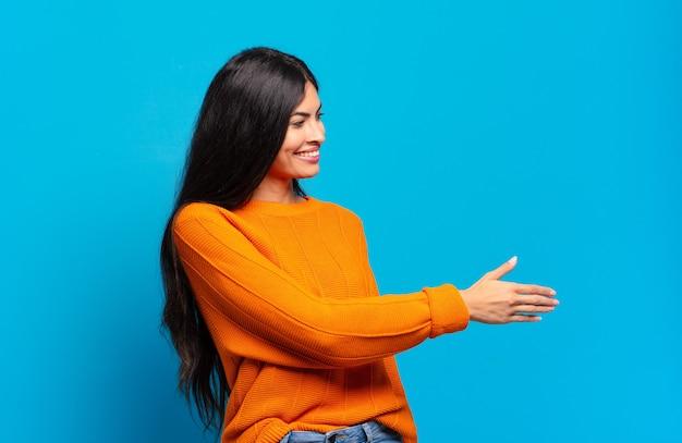 Jonge mooie spaanse vrouw die lacht, u begroet en een handschud aanbiedt om een succesvolle deal, samenwerkingsconcept te sluiten