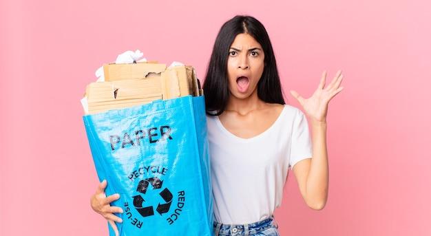 Jonge mooie spaanse vrouw die met handen in de lucht schreeuwt en een papieren zak vasthoudt om te recyclen