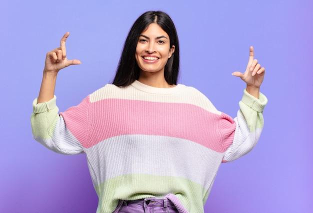 Jonge mooie spaanse vrouw die of eigen glimlach met beide handen omlijst of schetst, die positief en gelukkig kijkt, wellnessconcept