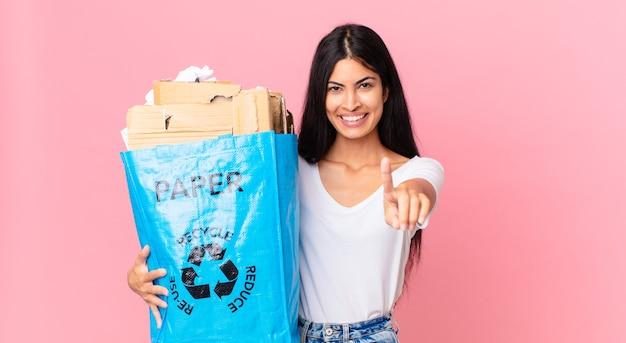 Jonge mooie spaanse vrouw die trots en zelfverzekerd glimlacht en nummer één maakt en een papieren zak vasthoudt om te recyclen