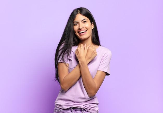 Jonge mooie spaanse vrouw die vrolijk lacht en viert, met gebalde vuisten en gekruiste armen, zich gelukkig en positief voelend