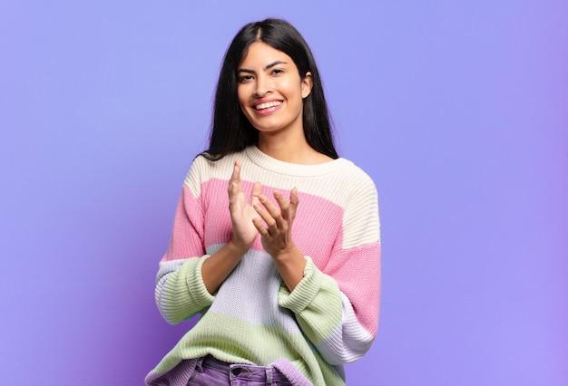 Jonge mooie spaanse vrouw die zich gelukkig en succesvol voelt, lacht en in de handen klapt, gefeliciteerd met een applaus