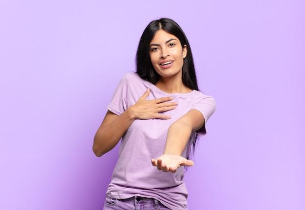 Jonge mooie spaanse vrouw die zich gelukkig en verliefd voelt, met één hand naast hart glimlacht en de andere vooraan uitgestrekt