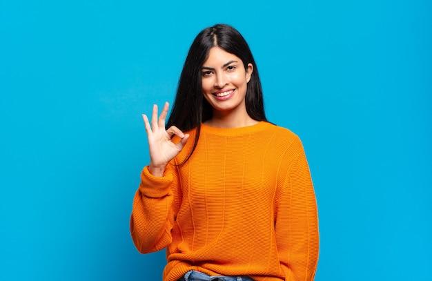 Jonge mooie spaanse vrouw die zich gelukkig, ontspannen en tevreden voelt, goedkeuring toont met ok gebaar, glimlachend