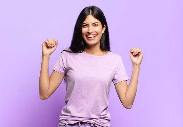 Jonge mooie spaanse vrouw die zich gelukkig, positief en succesvol voelt, overwinning, prestaties of veel geluk viert
