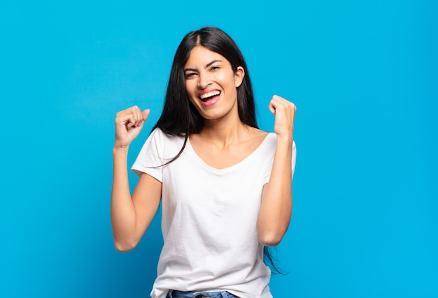 Jonge mooie spaanse vrouw die zich gelukkig, verrast en trots voelt, schreeuwt en succes viert met een grote glimlach