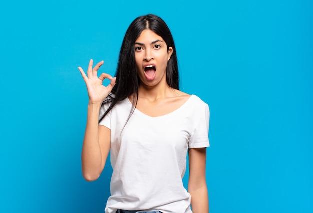 Jonge mooie spaanse vrouw die zich succesvol en tevreden voelt, glimlachend met wijd open mond, goed teken makend met de hand