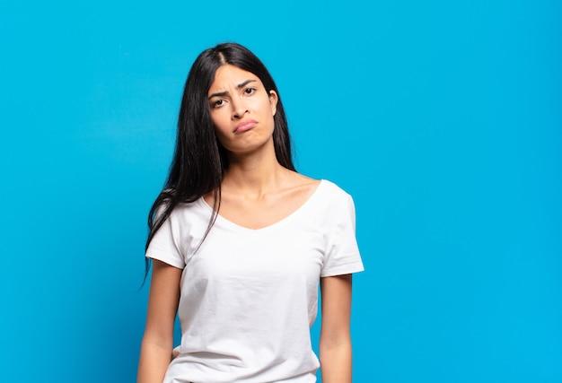 Jonge mooie spaanse vrouw die zich verdrietig en zeurderig voelt met een ongelukkige blik, huilend met een negatieve en gefrustreerde houding