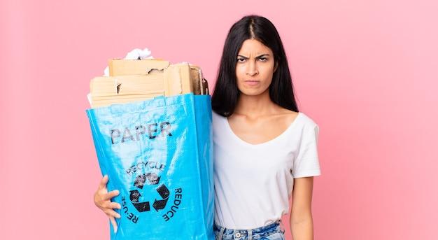 Jonge mooie spaanse vrouw die zich verdrietig, overstuur of boos voelt en opzij kijkt en een papieren zak vasthoudt om te recyclen