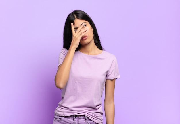 Jonge mooie spaanse vrouw die zich verveeld, gefrustreerd en slaperig voelt na een vermoeiende, saaie en vervelende taak, gezicht met de hand vasthoudend