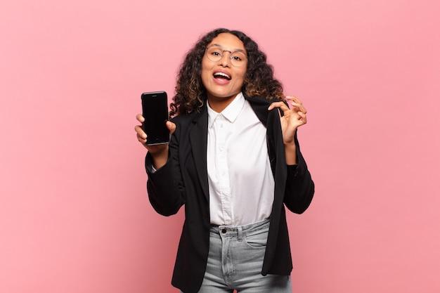 Jonge mooie spaanse vrouw gelukkig en trots bedrijf en smartphone concept