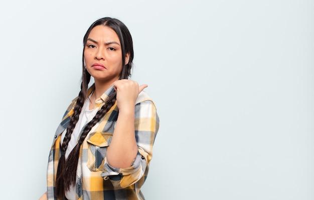 Jonge mooie spaanse vrouw met een exemplaarruimte tegen geïsoleerde muur