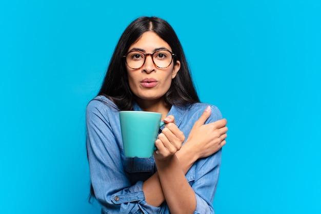 Jonge mooie spaanse vrouw met een kopje koffie