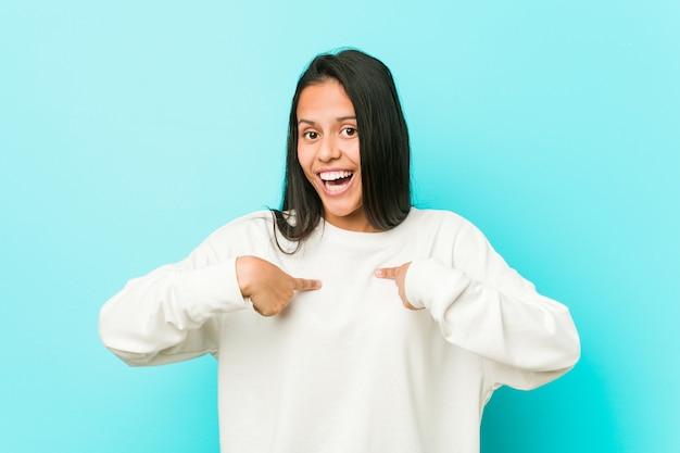 Jonge mooie spaanse vrouw verrast wijzend met vinger, breed glimlachend.
