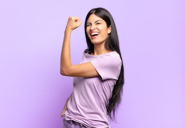 Jonge mooie spaanse vrouw voelt zich gelukkig, tevreden en krachtig, buigt fit en gespierde biceps, ziet er sterk uit na de sportschool