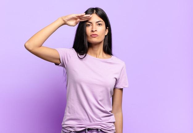 Jonge mooie spaanse vrouwengroet met een militaire groet in een daad van eer en patriottisme, die respect toont