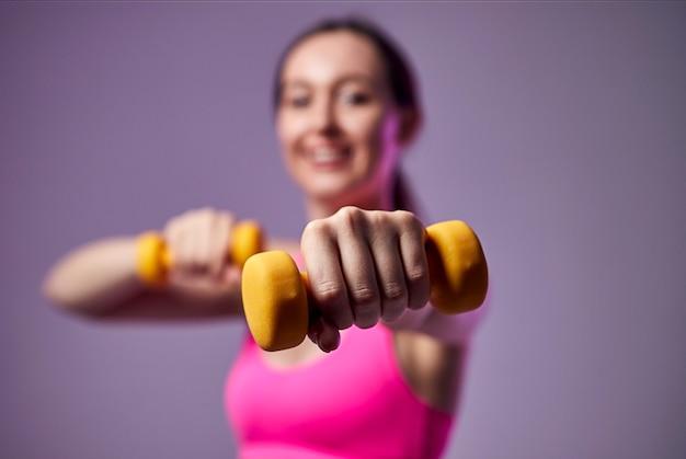Jonge mooie sport meisje in beenkappen en een top doet oefeningen met halters. gezonde levensstijl.