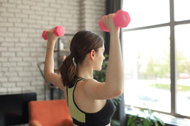 Jonge mooie sport meisje in legging en een top doet oefeningen met halters. gezonde levensstijl. een vrouw gaat thuis sporten.