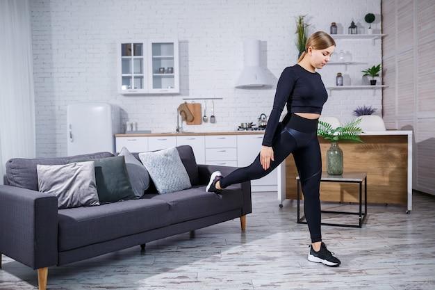 Jonge mooie sport meisje in legging en een top doet oefeningen thuis op de bank. gezonde levensstijl. de vrouw gaat thuis sporten.
