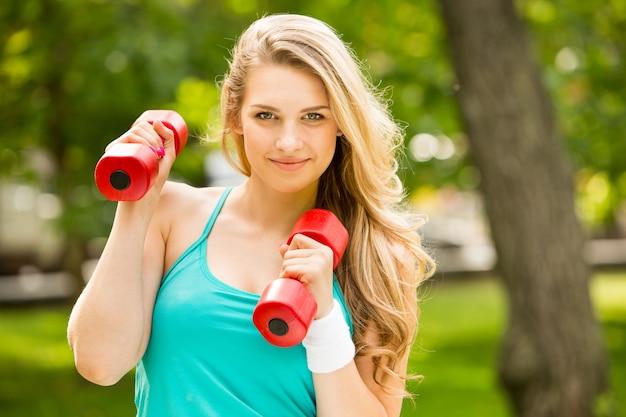 Jonge mooie sport meisje met halters in het park op een achtergrond van groen gras