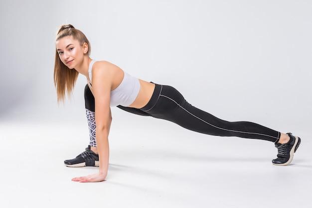 Jonge mooie sport vrouw die zich uitstrekt geïsoleerde benen