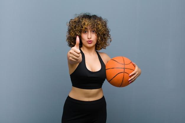 Jonge mooie sportenvrouw die fitness kleren met een mandbal draagt
