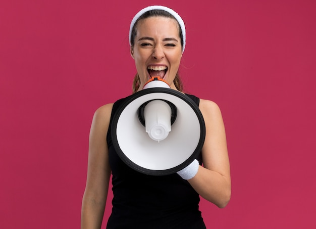 Jonge mooie sportieve meid met hoofdband en polsbandjes die in luidspreker schreeuwen