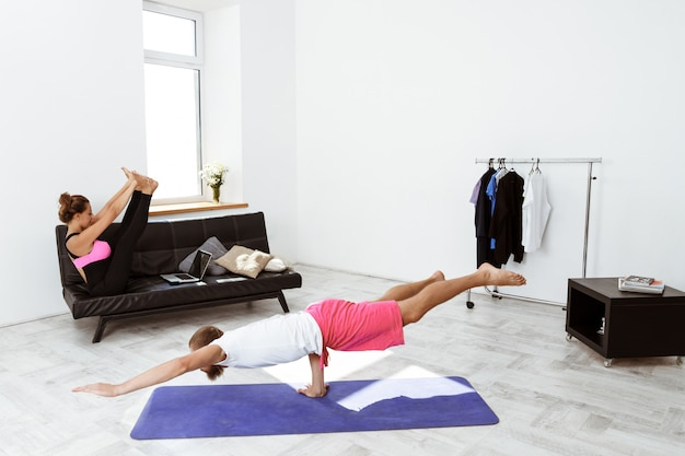 Jonge mooie sportieve paar asana training yoga thuis.