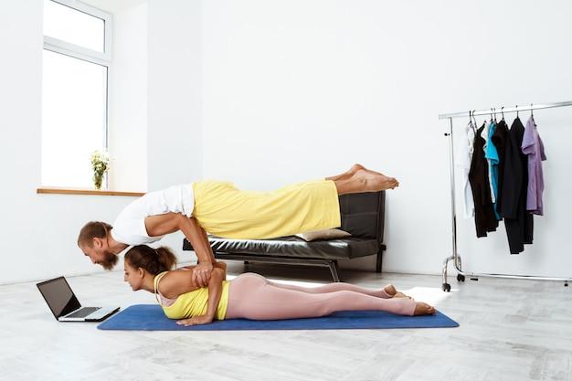Jonge mooie sportieve paar yoga asana's van de opleidingspartner thuis.