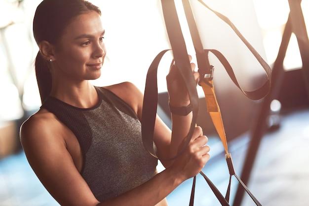 Jonge, mooie sportieve vrouw die trx-fitnessriemen aanpast tijdens het sporten in de sportschool