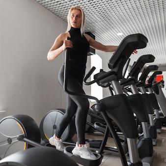 Jonge mooie sportieve vrouw in zwarte stijlvolle kleding in sneakers doet cardiotraining op een simulator in de sportschool.