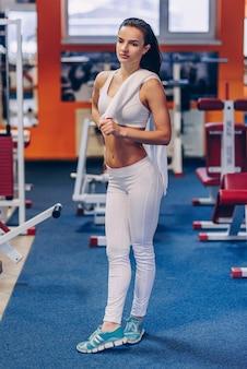 Jonge mooie sportieve vrouw met perfect lichaam die trainingen in een gymnastiek doen
