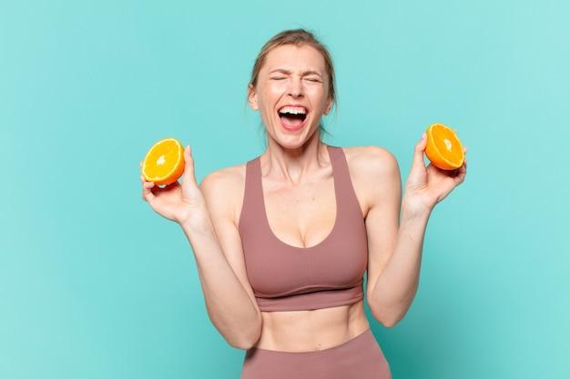 Jonge mooie sportvrouw boze uitdrukking en een sinaasappel houden
